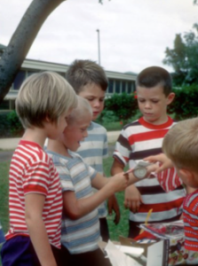 Clad in what looks like a matching striped t-shirt, Jim Simpson and other party guests admire a Duncan Yo-Yo, one of Mike's many birthday presents.
